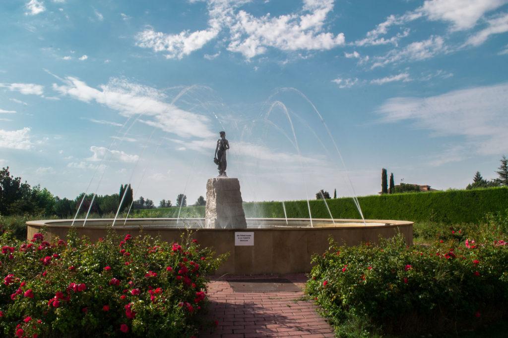 Fuente de la residencia Ciudad de Aranda, amplia y circular con estatua central de una mujer, todo ello rodeado de rosales.
