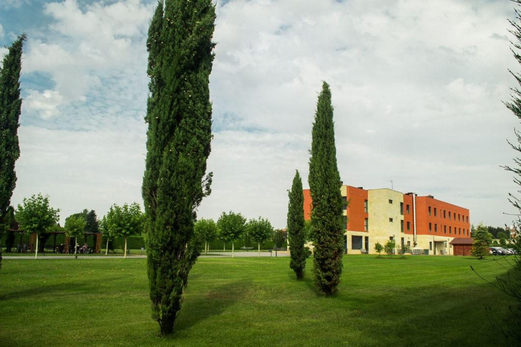 Jardines en Residencia Ciudad Aranda, con explanada de cesped y cipreses, y al fondo el edificio y pérgola.