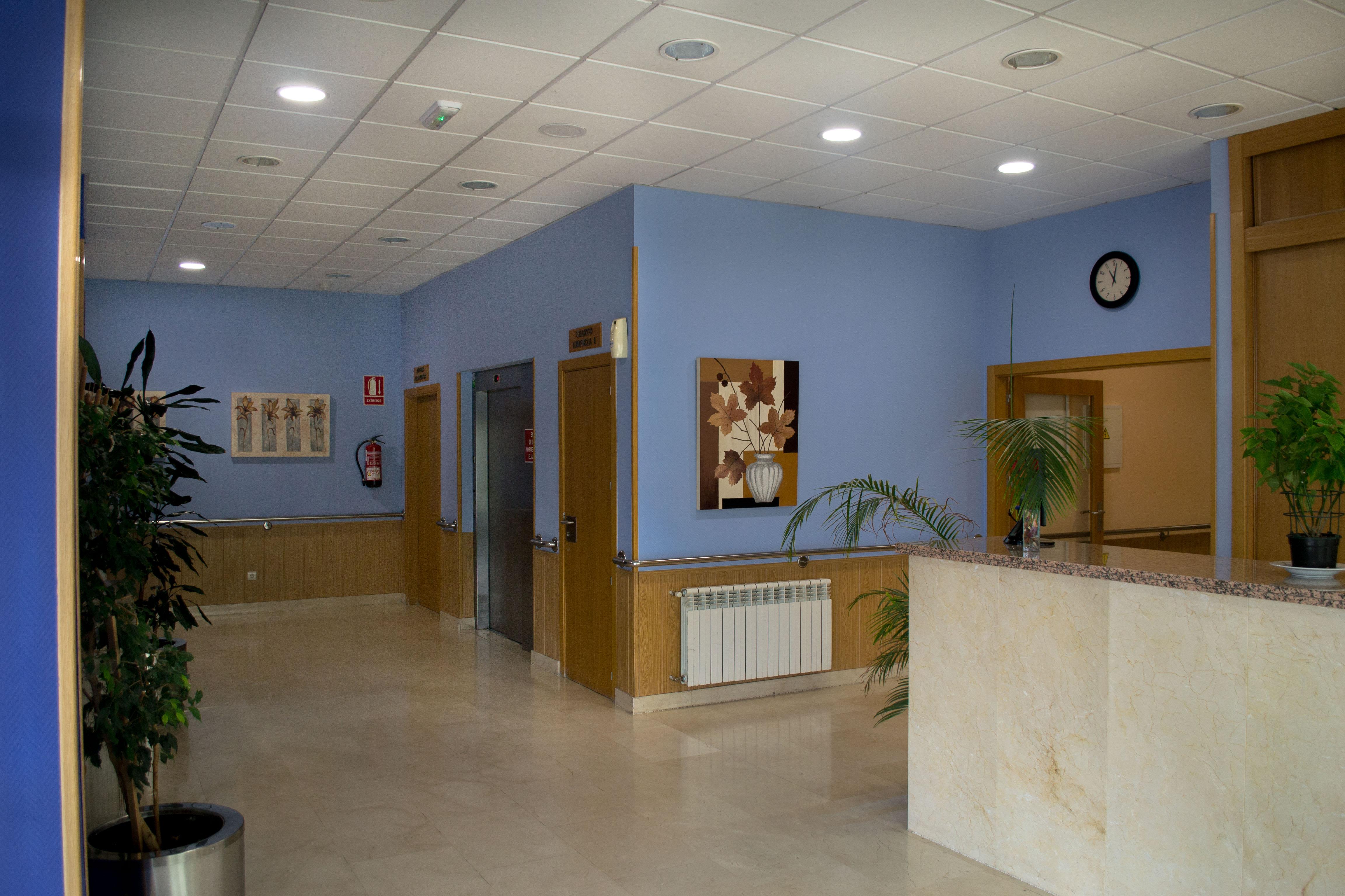Recepción en la Residencia Cuidad de Aranda, con suelos amarmolados, ascensor y decoración con cuadros y plantas naturales.