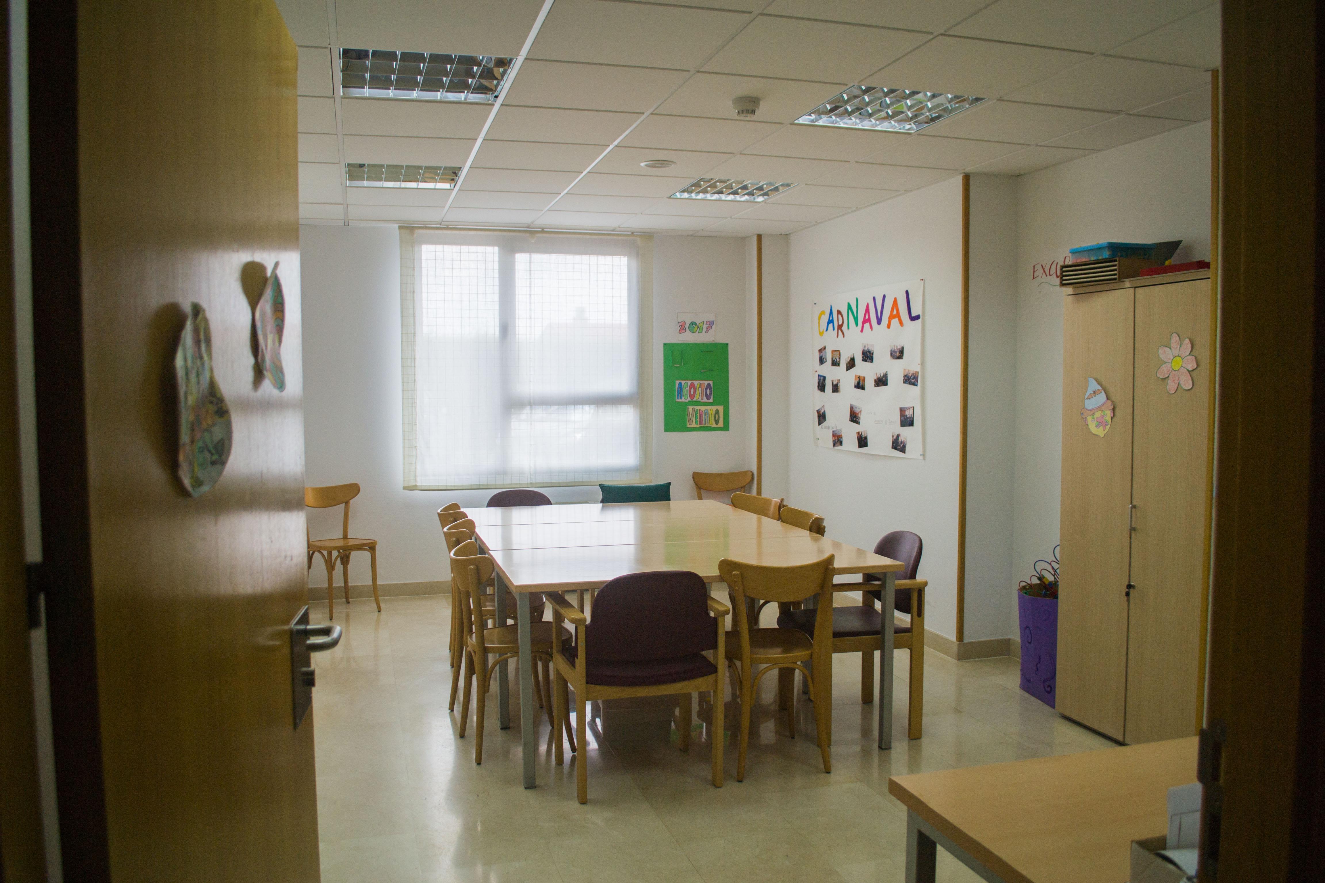 Sala de terapia ocupacional en Residencia Ciudad de Aranda, con mesa central y sillas alrededor, armarios para almacenar material y carteles con creaciones y fotos de los residentes.