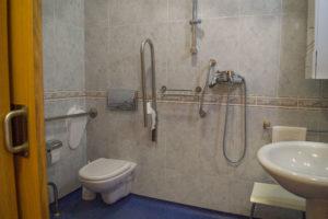 Baño geriátrico individual en residencia Ciudad de Aranda, con wc, ducha con asiento, armario y lavabo, con múltiples dispositivos de agarre y suelo antideslizante para comodidad y seguridad.