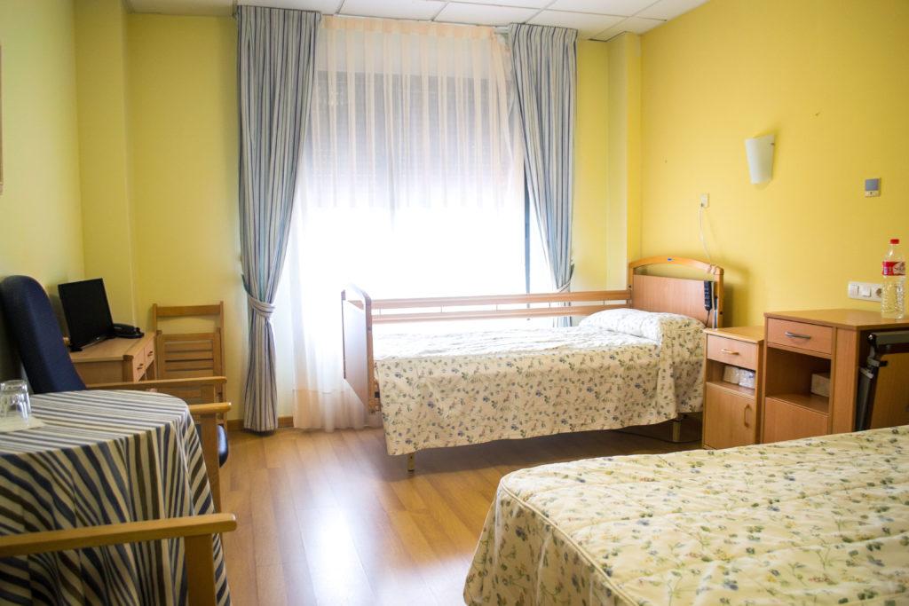 Habitacion doble en residencia Ciudad de Aranda, con dos camas individuales con barras laterales separadas por mesillas, ventana amplia con cortinas, mueble de televisión, mesa camilla y sillas para sentarse.